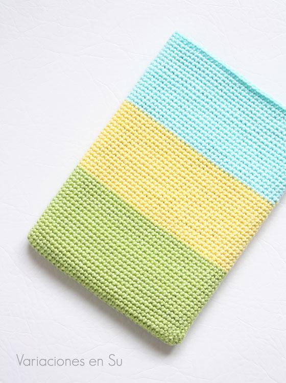 Funda de ganchillo para libro electrónico (e-reader) tejida con hilo de algodón en los colores verde, amarillo y azul.