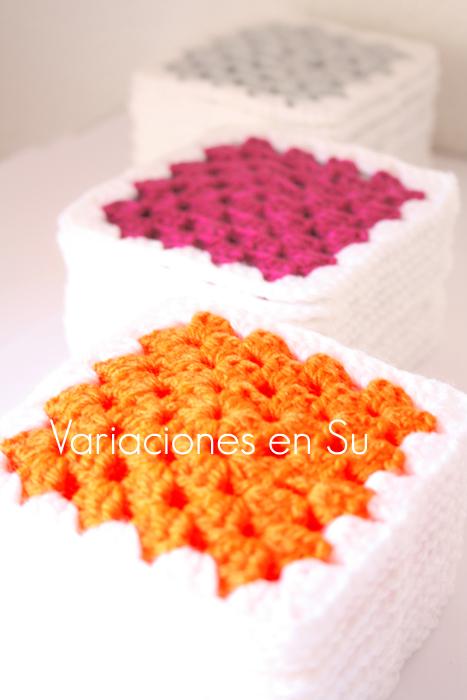 Pilas de granny squares o cuadrados de ganchillo tejidos en los colores naranja, magenta y gris.