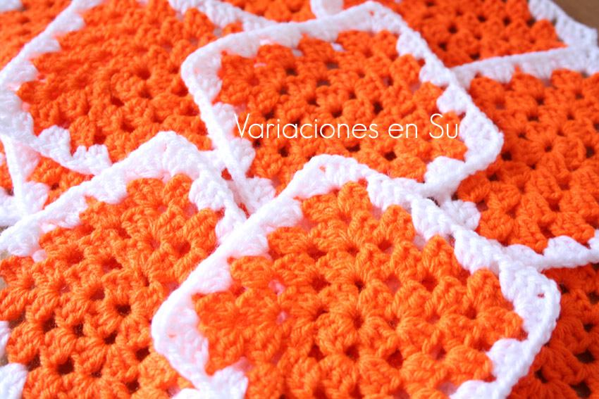 Granny squares o cuadrados de ganchillo tejidos en lana de color naranja.