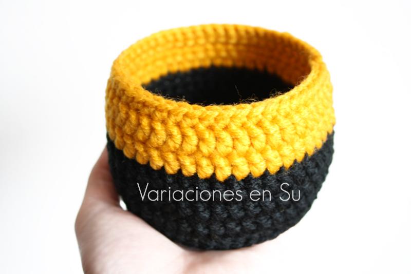Cesta de ganchillo, de forma circular, tejida en lana de colores amarillo y negro.