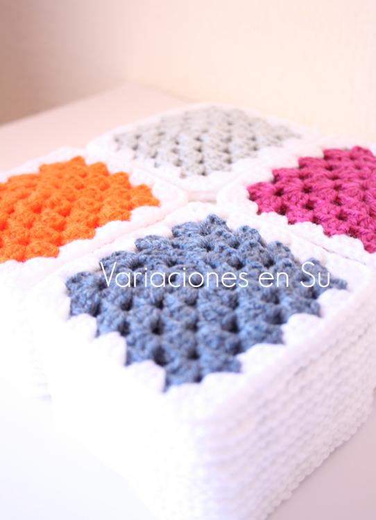 Pilas de granny squares o cuadrados de ganchillo tejidas en lana de colores azul dénim, naranja, magenta y gris.