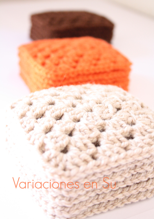 Granny squares o cuadrados tejidos a ganchillo en lana de los colores marrón, naranja y beige.