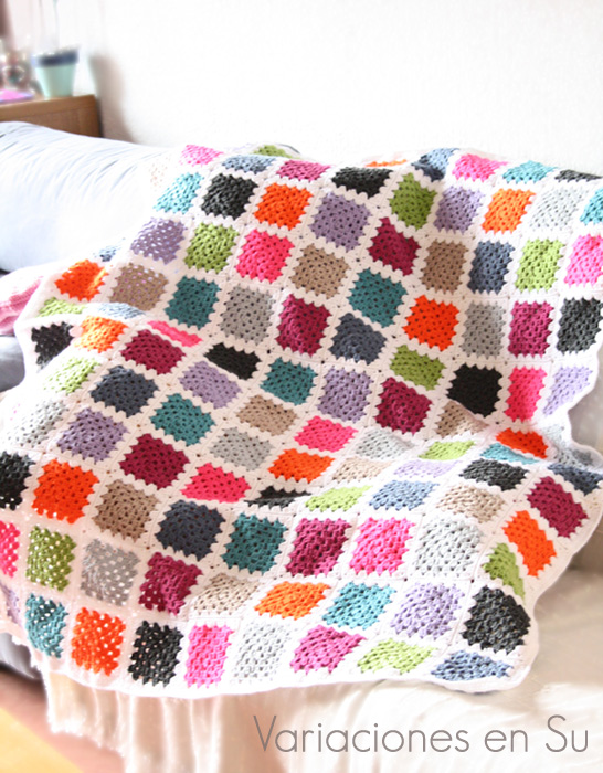Manta de ganchillo hecha con granny squares en lana de varios llamativos colores.