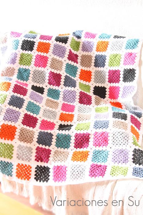 Manta de granny squares o cuadrados de ganchillo tejidos en lana de llamativos colores.