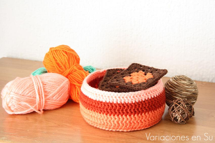 Cesta de ganchillo de forma circular, tejida en lana de tonos naranjas.