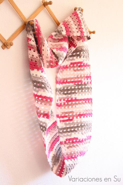 Bufanda de ganchillo tejida en punto calado con lana de tonos grises y rosas.