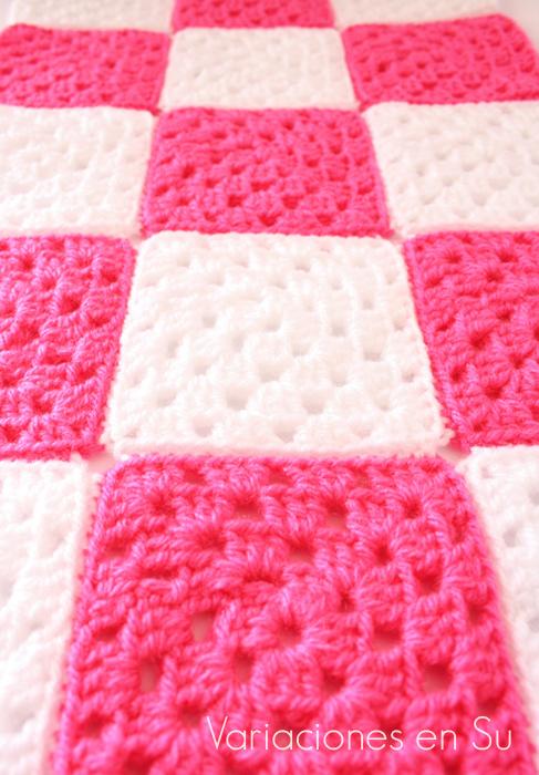 Granny squares o cuadrados de ganchillo tejidos en lana de colores rosa y blanco.