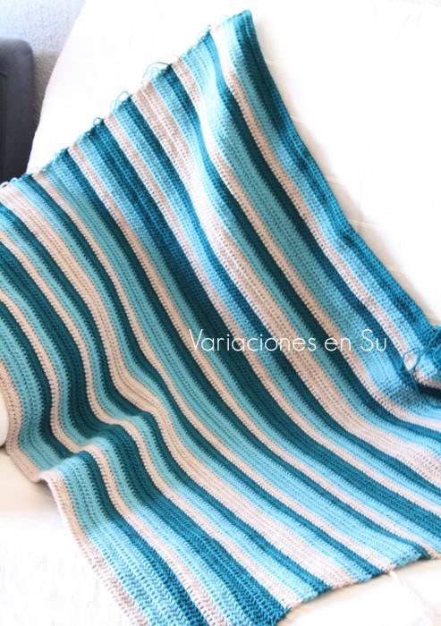 Manta de ganchillo a rayas tejida en lana de tres colores, en tonos azules y piedra.