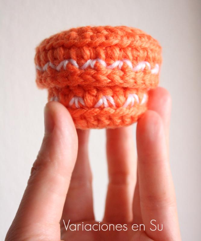 Caja de ganchillo pequeña, de forma circular y con tapa incluida, tejida en lana de color naranja con bordados en blanco.
