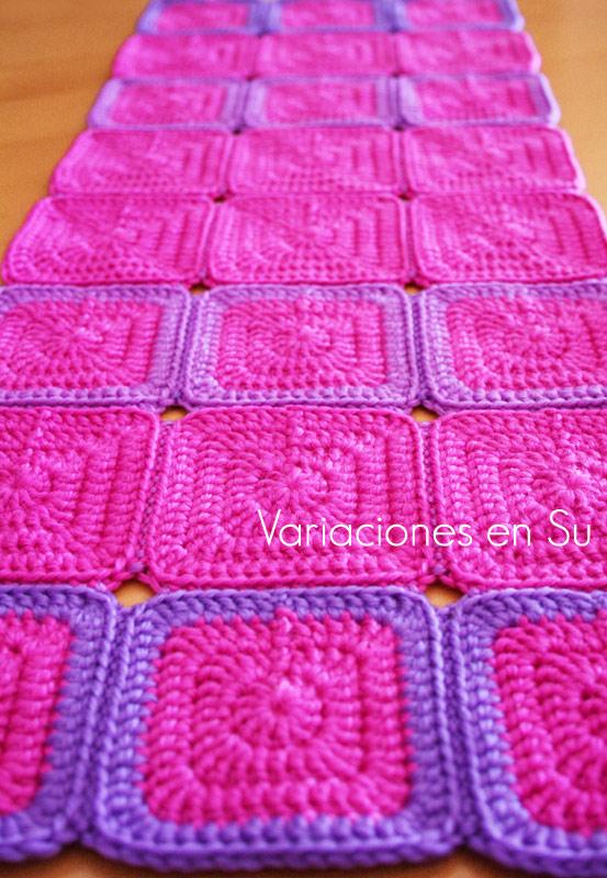 Camino de mesa de ganchillo hecho a partir de granny squares en los colores fucsia y malva.