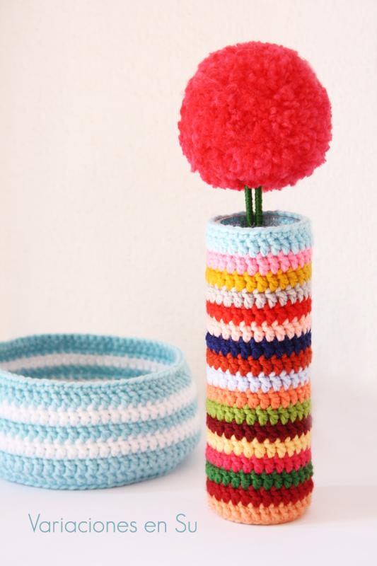 Funda de ganchillo para jarrón tejida en lana de muchos colores y flor grande de color rojo en forma de pompón.