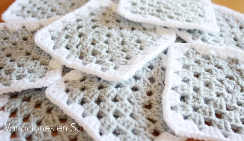 Granny squares o cuadrados de ganchillo tejidos en lana de color gris perla.