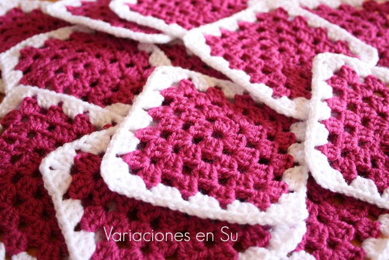 Granny squares o cuadrados de ganchillo tejidos en lana de color magenta.