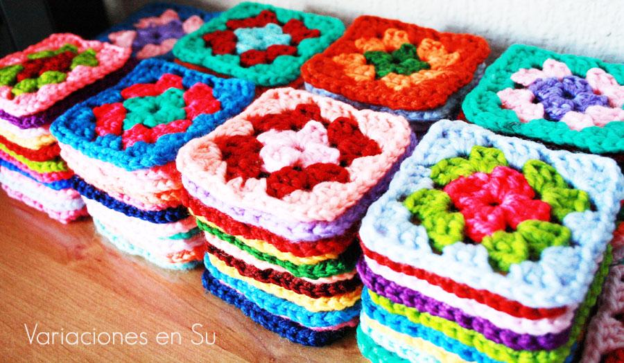 Pilas de cuadrados de ganchillo tejidos en varios colores.