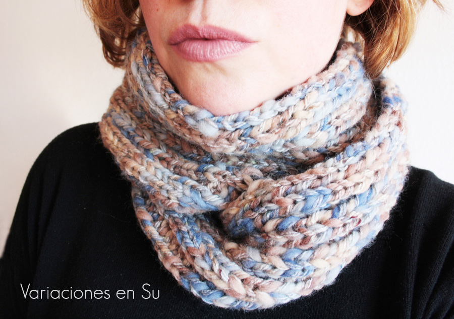 Bufanda de punto tejida a dos agujas en tonos azules y marrones.
