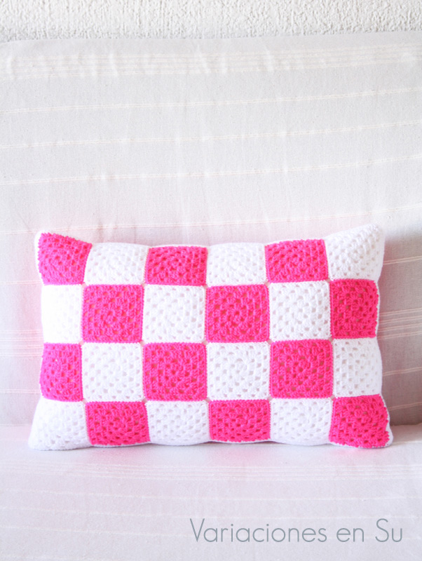 Cojín de ganchillo formado por granny squares o cuadrados, y tejido en los colores rosa flúor y blanco. Detalle de la cara A.
