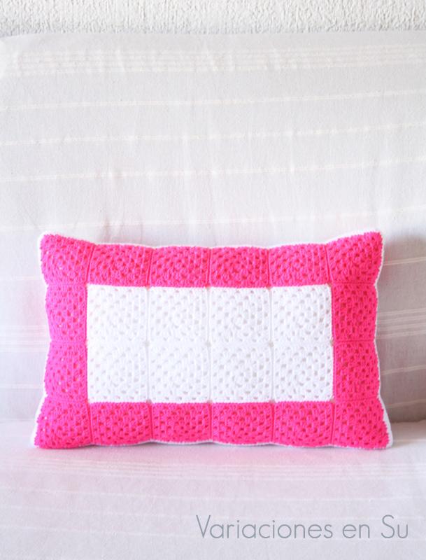 Cojín de ganchillo formado por granny squares o cuadrados, y tejido en los colores rosa flúor y blanco. Detalle de la cara B.