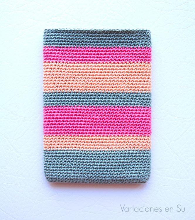 Funda de ganchillo para e-reader tejida con hilo de algodón en los colores gris, rosa y salmón.