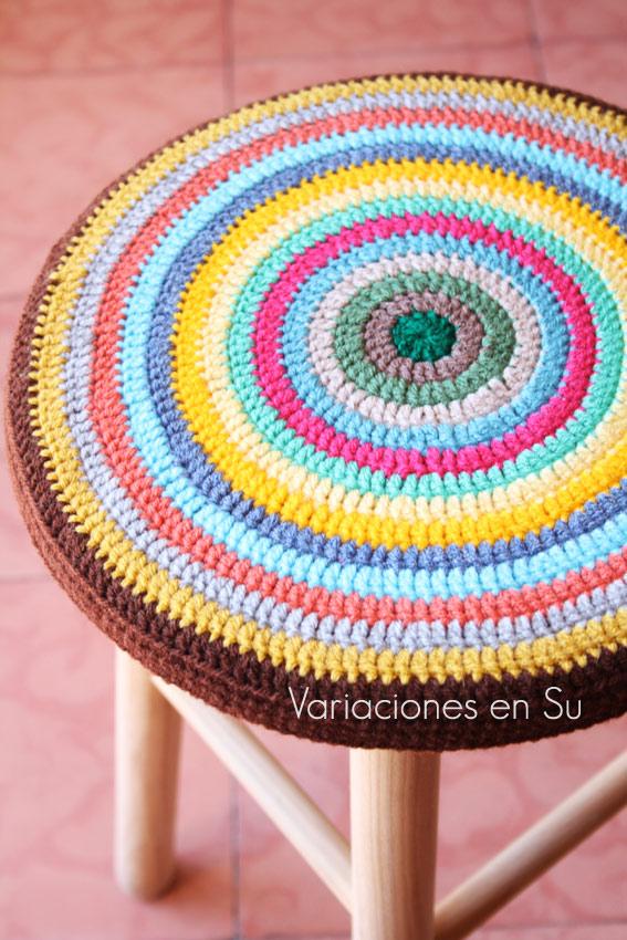 Funda de ganchillo para taburete, de forma circular, tejida en alegres colores y con el borde en marrón.