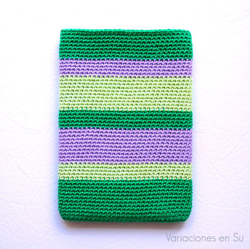 Funda de ganchillo para e-reader tejida con hilo de algodón mercerizado en los colores verde botella, verde pistacho y malva.