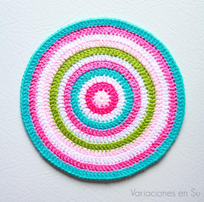 Mandala de ganchillo tejida en alegres colores rosas, azul, verde y blanco.
