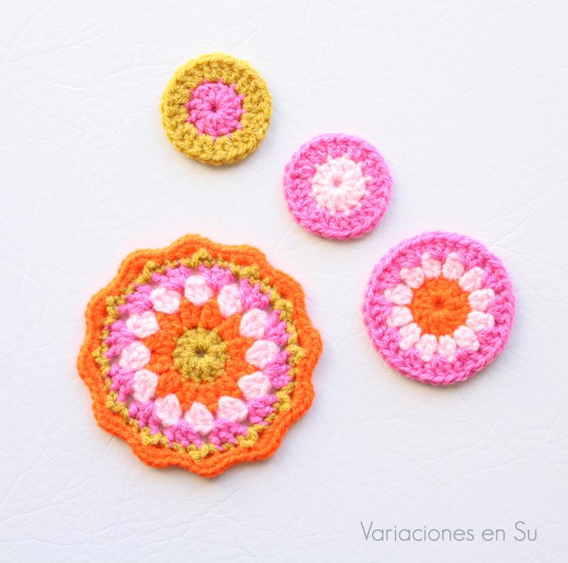 Set de posavasos de ganchillo en proceso, tejido en rosas, naranja y amarillo mostaza.