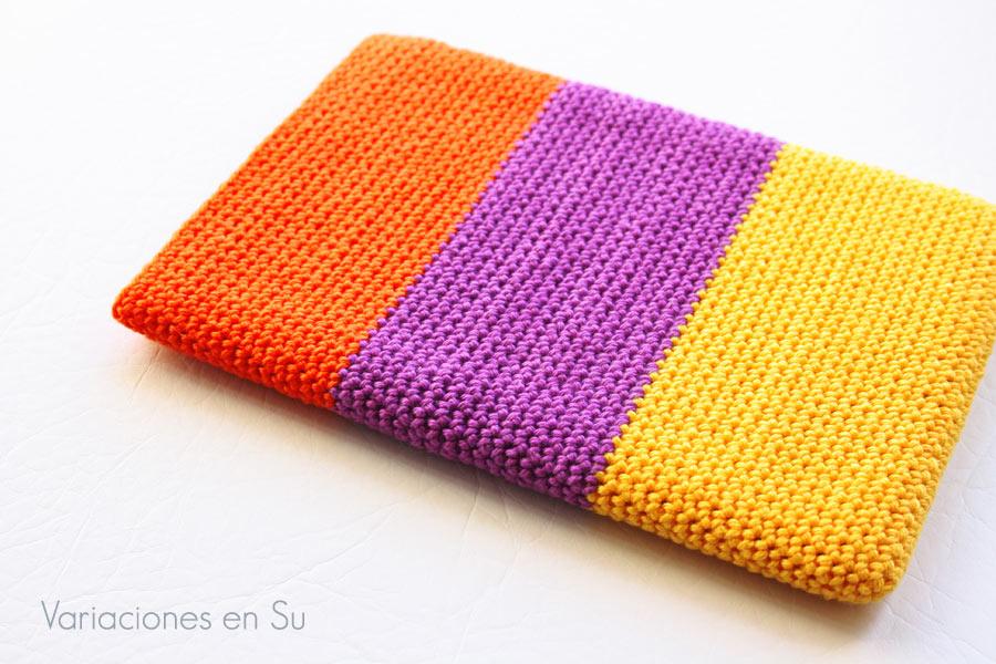 Funda de ganchillo para libro electrónico (e-reader) tejida en los colores naranja, violeta y amarillo.