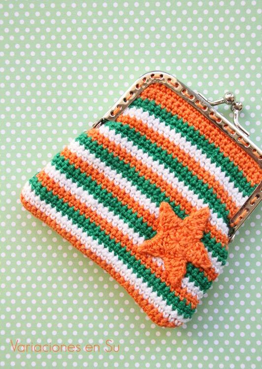 Monedero de ganchillo tejido a rayas en los colores naranja, verde y blanco, con figura de estrella en naranja y boquilla plateada.