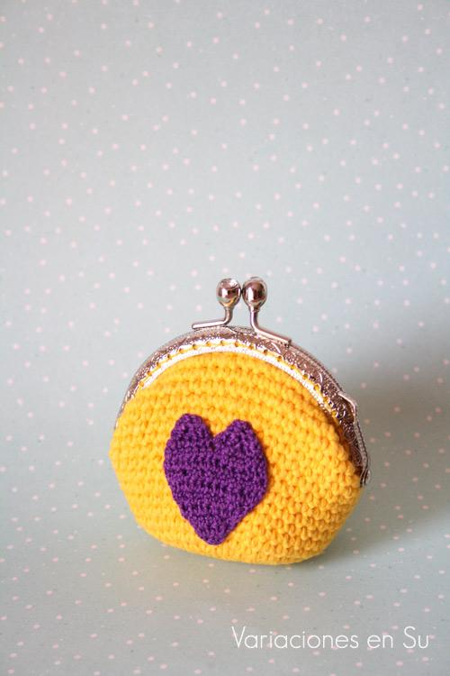 Monedero de ganchillo en amarillo con figura de corazón en violeta. Está acabado con una boquilla metálica plateada con filigrana.