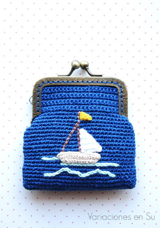 Monedero de ganchillo con figura de barco en la parte frontal y boquilla metálica de color bronce con filigrana.