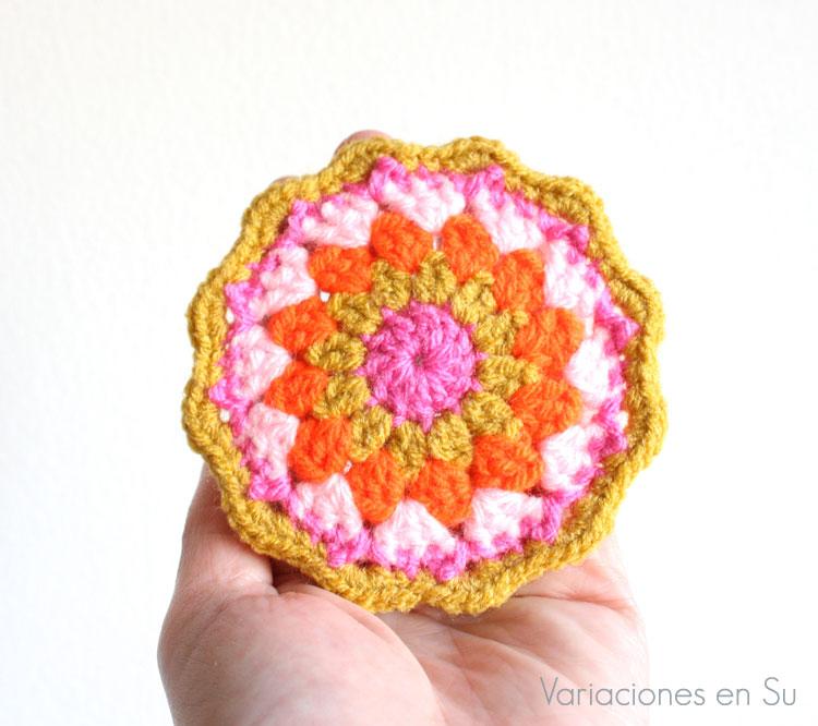 Posavasos tejido a ganchillo en tonos rosa, naranja flúor y amarillo mostaza.