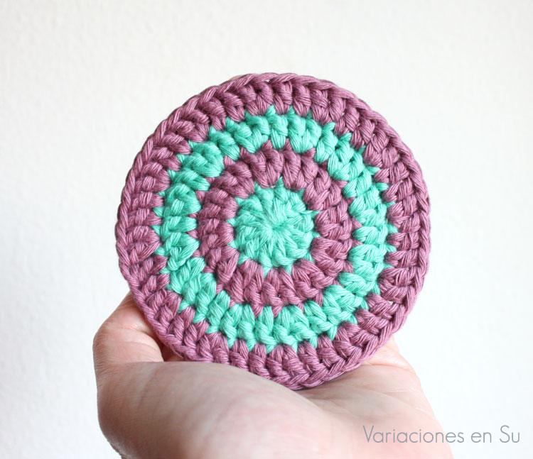 Posavasos de ganchillo tejido con hilo de algodón en los colores verde y malva.