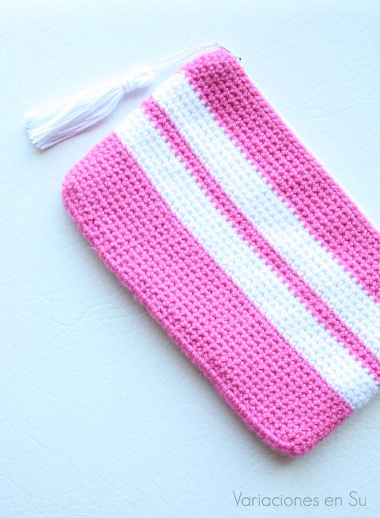 Neceser de ganchillo en rosa y blanco, con cierre de cremallera y borla decorativa.