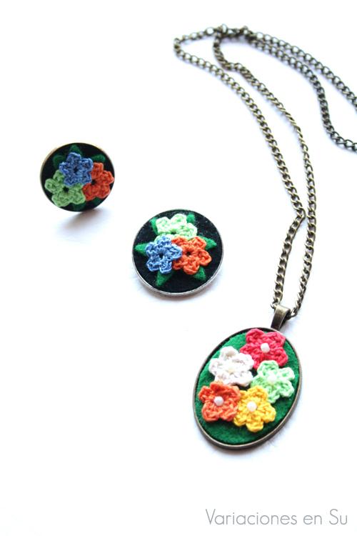Conjunto de collar, broche y anillo decorados con flores de ganchillo en varios colores.
