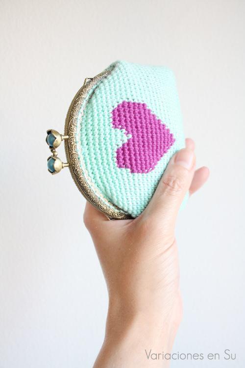 Monedero de ganchillo en azul con figura de corazón en violeta. Está acabado con una boquilla metálica de color bronce con filigrana y cierre en forma de flor.