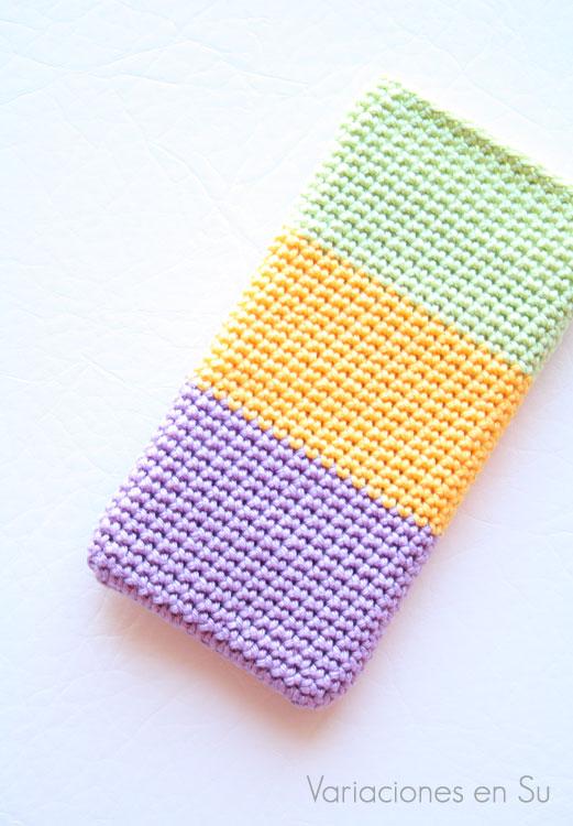 Funda para móvil tejida a ganchillo con hilo de algodón mercerizado en los colores malva, amarillo y verde.