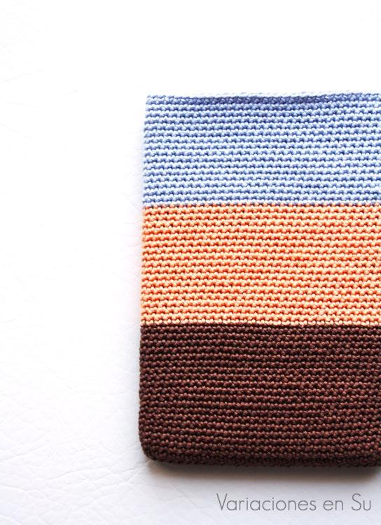Funda de ganchillo para libro electrónico (e-reader) tejida con hilo de algodón en los colores marrón chocolate, salmón y azul celeste.