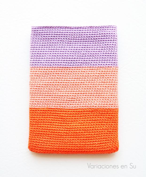 Funda de ganchillo para libro electrónico tejida con hilo de algodón en los colores naranja, salmón y malva.